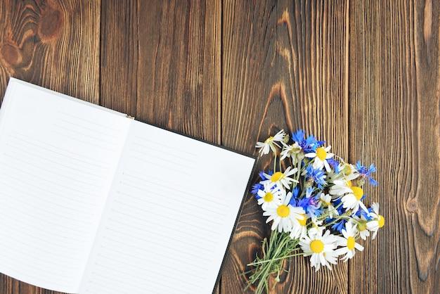 Fotocamera, taccuino e fiori di campo su fondo di legno scuro. libero professionista. guadagni nella foto.