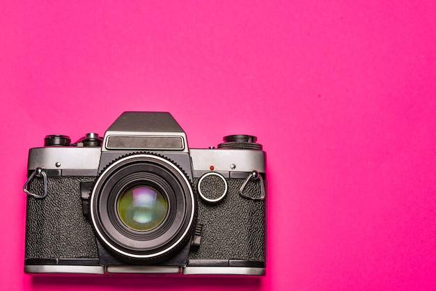 Fotocamera su uno spazio rosa. concetto di viaggio e fotografo
