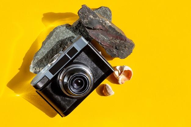 Fotocamera, conchiglie e pietre su uno sfondo giallo brillante. sfondo estivo con luce solare intensa. concetto di viaggio e vacanza.