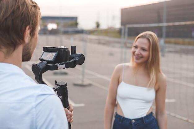 Il cameraman sta filmando la blogger per strada