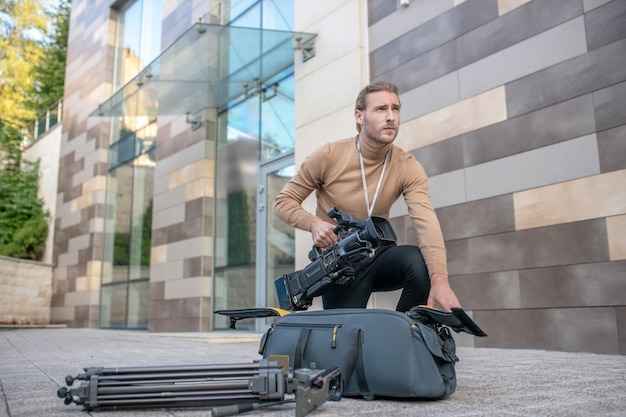 Cameraman che estrae l'attrezzatura dalla custodia
