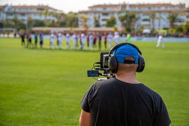 Cineoperatore con videocamera riprese video sulla partita di calcio