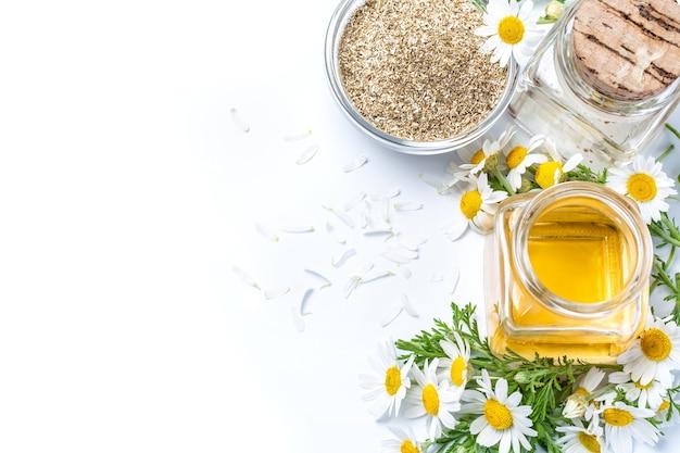 Olio di camomilla in bottiglia di vetro con fiori isolati su bianco