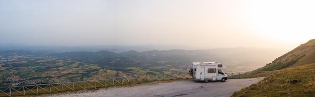 Camper sul lato della strada nel bellissimo paesaggio. cielo drammatico al tramonto, nuvole panoramiche sopra gli altopiani unici e la catena montuosa in italia, concetto di vacanza vanlife alternativo.