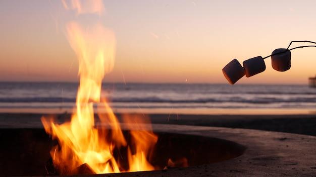 Fossa per falò in california usa. fuoco da campo sulla spiaggia del mare dell'oceano, toast marshmallow sul falò.