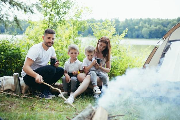 Campeggio in riva al lago nel bosco. famiglia felice papà mamma e bambini piccoli seduti accanto al fuoco e alla tenda nella natura. trascorrere il tempo libero insieme in vacanza. all'aperto. genitori con bambini che tengono una tazza