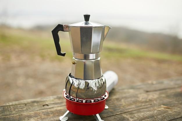 Caffè da campeggio all'aperto con caffettiera geyser in metallo su fornello a gas, passo dopo passo.