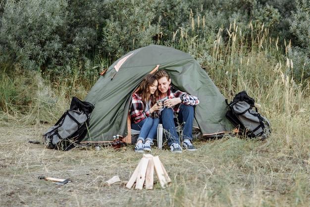 Campeggio coppia uomo e donna viaggiatori che bevono tè accanto al fuoco nella campagna vicino alla tenda