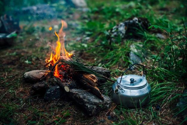 Bollitore da campeggio vicino a un piccolo fuoco da campo