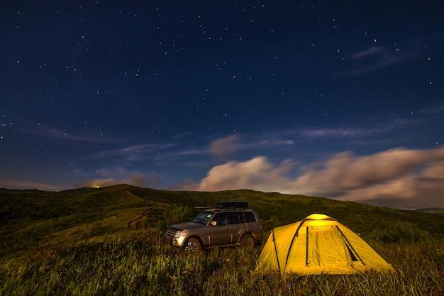 Campeggio in un prato sotto il cielo notturno. esiste un po' di rumore da iso elevati.