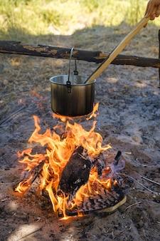 Campeggio, una pentola d'acqua bolle sul fuoco.