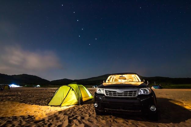 Campeggio sulla spiaggia di sabbia sotto le stelle nella notte. esiste un po' di rumore da alti iso