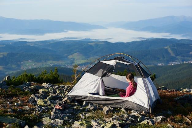 Accampandosi sulla cima della montagna sulla mattina luminosa dell'estate