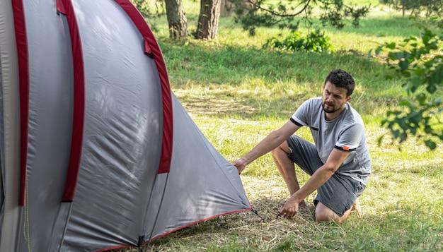 Campeggio, viaggio, turismo, concetto di escursione - giovane che installa tenda nella foresta.