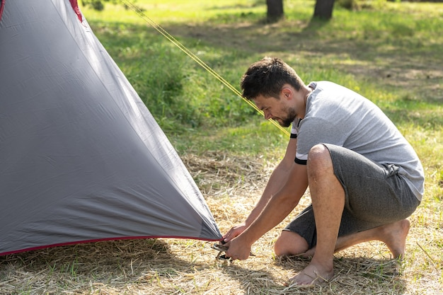 Campeggio, viaggi, turismo, concetto di escursione - giovane che installa tenda all'aperto.