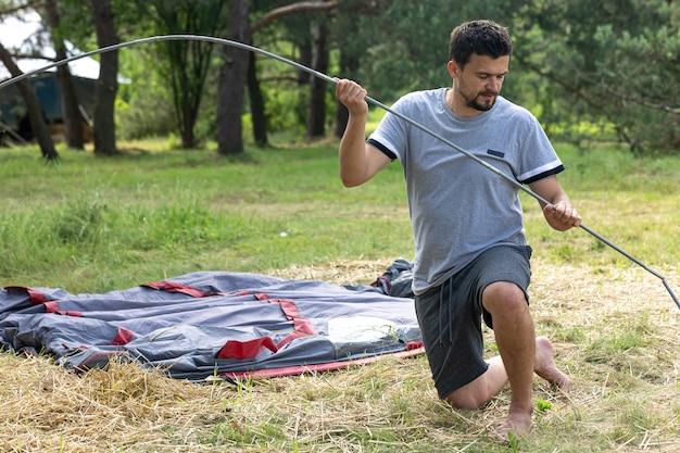 Campeggio, viaggio, turismo, concetto di escursione - giovane che installa tenda all'aperto.