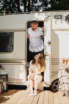 Campeggio e viaggi. coppie felici che si rilassano all'aperto vicino al rimorchio uomo e donna nel loro viaggio su strada