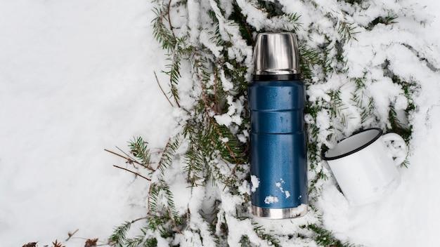 Campeggio nel concetto di foresta invernale. thermos e tazza di ferro sdraiato su un ramo di pino nella neve. vista dall'alto, copia dello spazio. borraccia sottovuoto da viaggio.