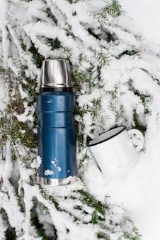 Campeggio nel concetto di foresta invernale. thermos e tazza laccata sdraiata su un ramo di pino nella neve. vista dall'alto, angolo verticale. borraccia sottovuoto da viaggio