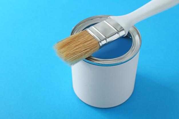 Barattolo di vernice e pennello sul blu