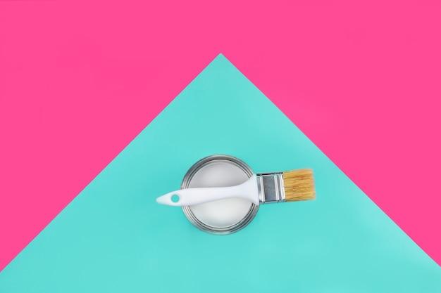 Barattolo di vernice con pennello su di loro su rosa e blu