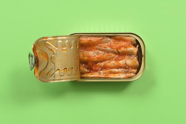 Lattina di sardine con salsa di pomodoro su sfondo rosso