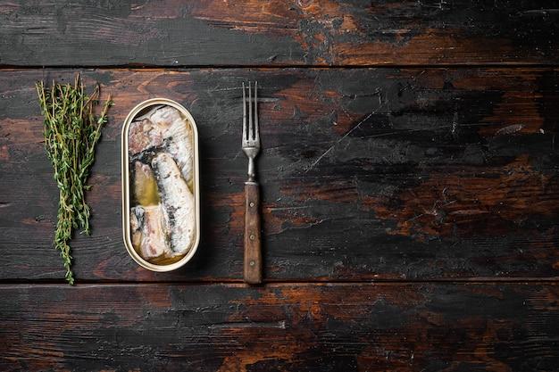 Lattina di sardine in set di olio d'oliva, su vecchio sfondo di tavolo in legno scuro, vista dall'alto piatta, con spazio di copia per il testo