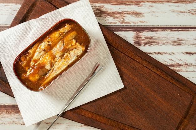 Lattina di sardine in salsa di pomodoro su un tavolo. vista dall'alto