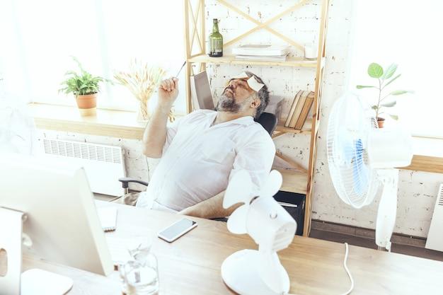 Non riesco a concentrarmi. uomo d'affari, manager in ufficio con computer e ventola di raffreddamento, sensazione di caldo. usando la ventola ma soffrendo ancora del clima scomodo nell'armadio. estate, lavoro d'ufficio, affari.