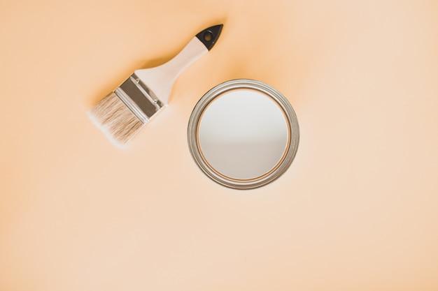 Barattolo di vernice bianca con un pennello, su uno sfondo luminoso.
