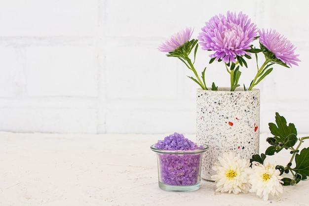 Possibile con sale marino e fiori di astri su sfondo bianco. cosmetici donna e accessori per il lavaggio.