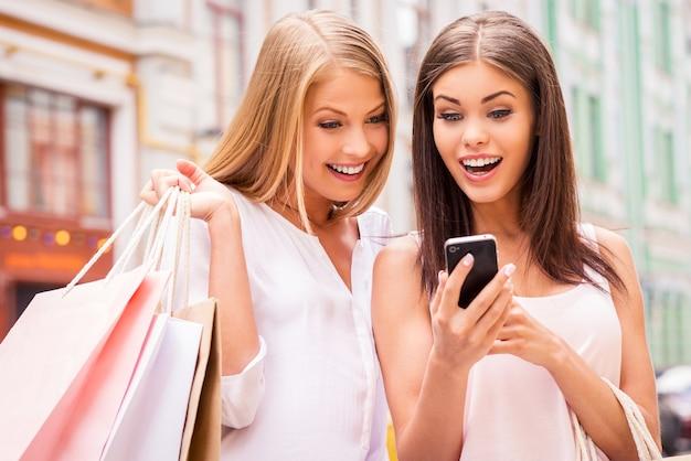 Riesci a immaginarlo? due giovani donne sorprese che tengono in mano le borse della spesa e guardano insieme il cellulare mentre stanno all'aperto