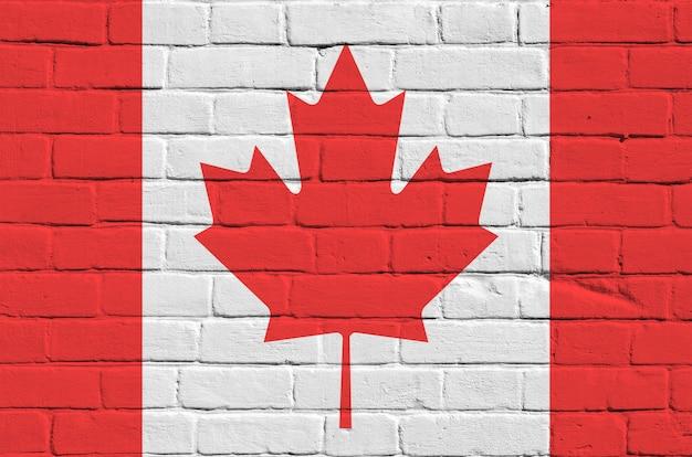 Bandiera del canada raffigurata nei colori della vernice sul vecchio muro di mattoni. insegna strutturata sulla grande muratura del muro di mattoni