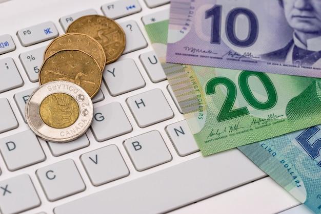 Dollaro canadese con il computer portatile - concetto di affari