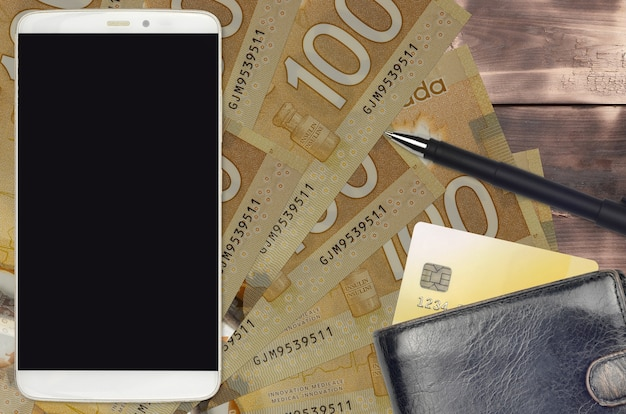 Banconote in dollari canadesi e smartphone con borsa e carta di credito