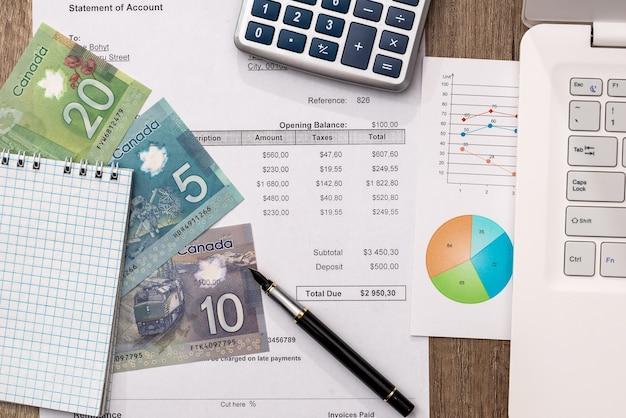 Soldi canadesi con laptop, documento, panoramica e calcolatrice