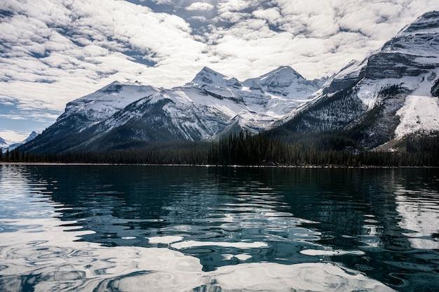 Montagne rocciose canadesi con la riflessione del cielo della nuvola sul lago maligne al parco nazionale di jasper, canada