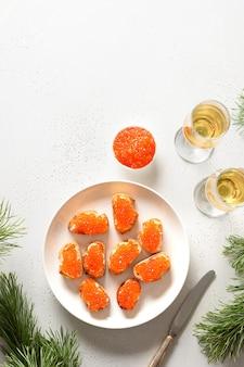 Canape con caviale rosso servito con champagne per capodanno o festa di natale sul tavolo bianco. formato verticale.