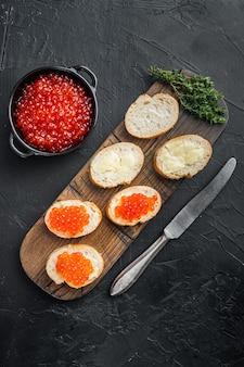 Crostino con caviale di salmone rosso, per capodanno, sulla tavola nera, vista dall'alto laici piatta