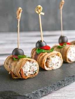 Crostini di melanzane fritte ripiene di formaggio, erbe aromatiche. guarnito con peperone dolce, prezzemolo e olive. su una tavola di ardesia nera. sfondo grigio. avvicinamento.