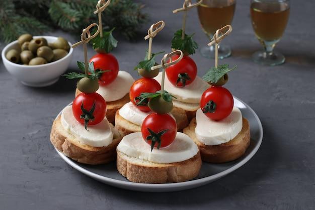 Crostini di mozzarella, pomodorini, olive verdi, prezzemolo su crostini di pane bianco su fondo grigio scuro. spuntino festivo di capodanno.