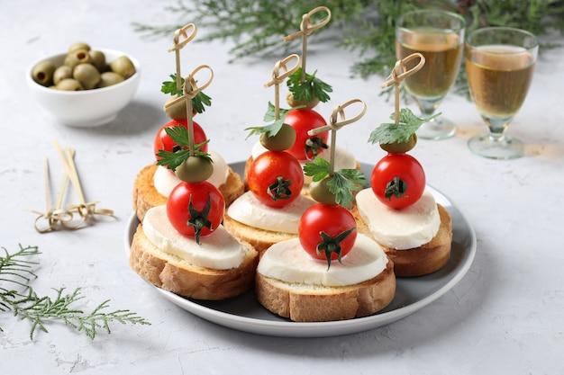 Tartine di mozzarella, pomodorini, olive verdi, prezzemolo su crostini di pane bianco