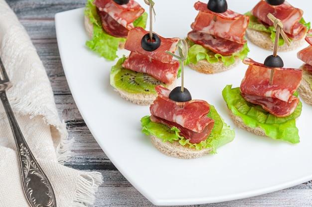 Crostini con carbonade, kiwi e lattuga su un pane bianco di grano. guarnito con olive. su un piatto bianco. vicino a una forchetta e un tovagliolo.