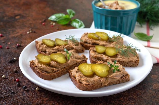 Crostini con patè di fegato di pollo e cetrioli sottaceto su pane di segale. antipasto gustoso e salutare.