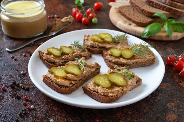 Crostini con patè di fegato di pollo e cetrioli sottaceto su pane di segale. antipasto gustoso e salutare