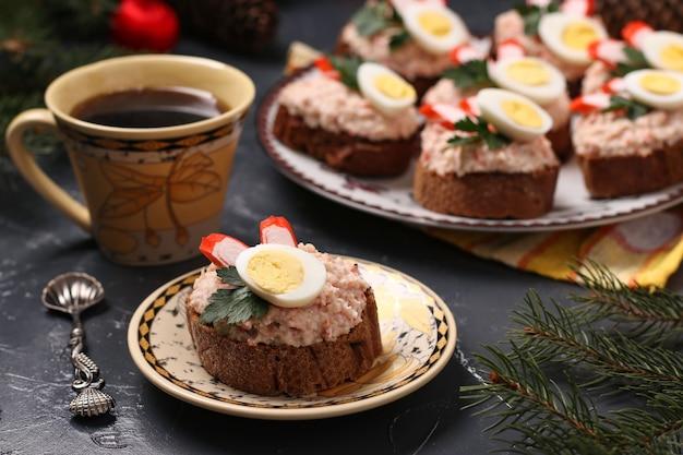Tartine con crema di formaggio, fagioli, bastoncini di granchio, uova di quaglia e tazza di caffè su sfondo scuro. avvicinamento