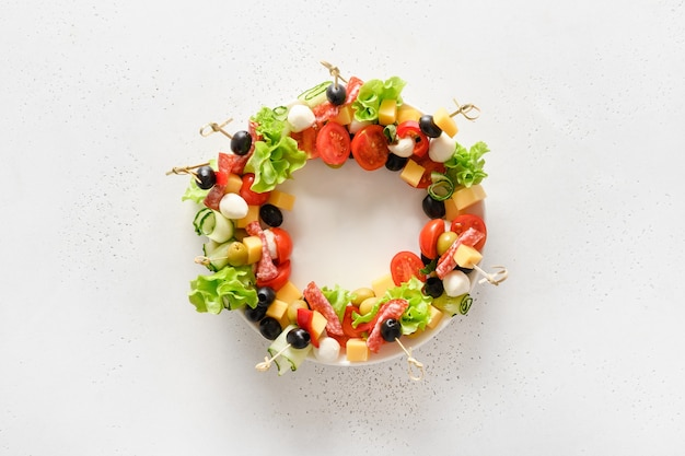 Tartine con verdure, olive, salame, snack di mozzarella come corona per la festa di natale.