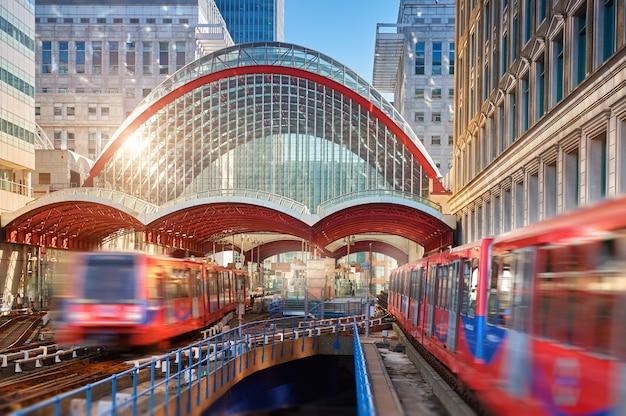 Canary wharf, stazione dlr. treno dlr che lascia la stazione in una giornata luminosa