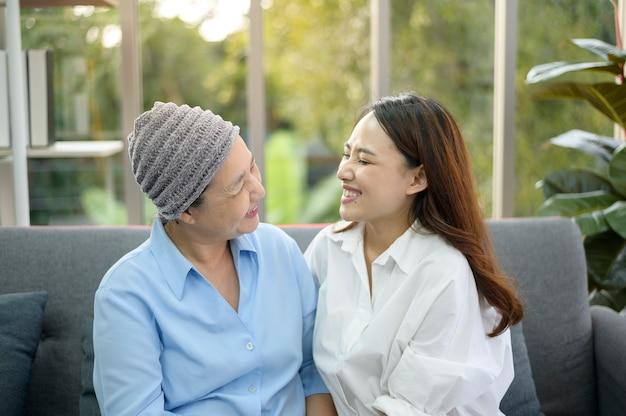 Una donna malata di cancro che indossa sciarpa capa che abbraccia la sua figlia solidale