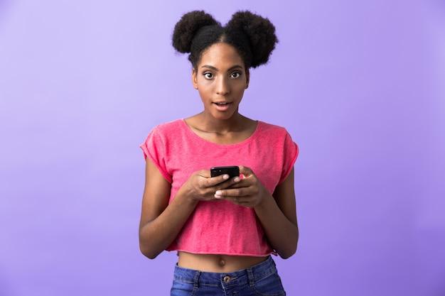 Candida donna afroamericana sorridente e tenendo il telefono cellulare, isolato